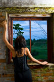 Goth girl looking out window. From an abandoned building Royalty Free Stock Images