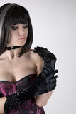 Goth girl in purple corset and black gloves. Studio shot over white background royalty free stock images