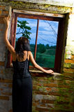 Goth girl at window. A lonely goth girl looking out of a window in some old premises Royalty Free Stock Photos