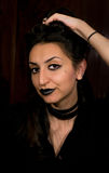 Goth style portrait of a female in black clothing and make up holding hair up Stock Images