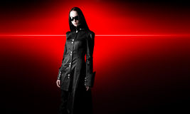 Goth woman in black cloak. On red shine background Stock Photo