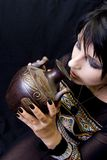 Goth Woman Drinks from a Vessel. A goth woman, perhaps a pagan priestess, drinks from an ancient vessel used in pagan rituals or ceremonies Stock Images