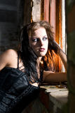 Goth woman leaning on window. A portrait of a goth woman leaning and looking out a broken window in an abandoned room royalty free stock photos