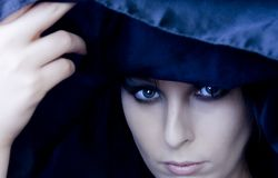 Goth Woman Under Black Scarf. A beautiful, young goth woman lifts a black scarf from over her head Stock Images