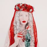 Gothic blonde woman vampire in flower wreath with pale skin and red lips. Rose in blood. Scary creepy witch with long hair. Gothic stock photos