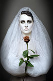 Gothic bride. Gothic girl in the white fop with the red flower Stock Image