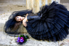 Gothic bride. In black wedding dress and veil lies Royalty Free Stock Image