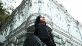 Gothic brunette girl standing in the middle of a street and glancing back. Low shot gothic brunette girl standing in the middle of a street and glancing back stock footage