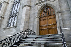 Gothic church entrance door stairway wide angle. Gothic church entrance wooden door and stairway wide angle view with snow in winter season Stock Image