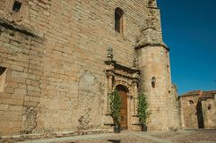 Gothic church facade with decorated wooden door at Caceres. Gothic church facade with decorated wooden door and plants in front of small square, in a sunny day stock photos