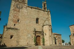 Gothic church facade with steeples and wooden door at Caceres. Gothic church facade with steeples and decorated wooden door in front of small square, in a sunny royalty free stock images