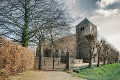 Gothic church with gate. A beautiful image of an old and historical church with early gothic bell tower and cast iron gate in front of it Royalty Free Stock Photography