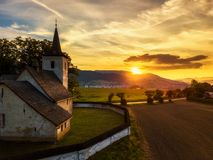 Gothic church at sunset in Slovakia. Gothic church at sunset with nearby town and mountains in the background in Liptov area, Slovakia Royalty Free Stock Photos