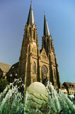 Gothic church with water fountain in fore ground. Gothic church with two tall towers and water fountain in fore ground Royalty Free Stock Image