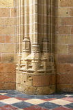 A gothic column base, with a tiles floor, against a wall Stock Photos