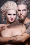 Gothic couple. Portrait of pierced tattooed man and woman with old-fashioned make-up and hairstyle Stock Image