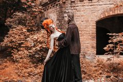 Gothic couple in halloween costume. Punk vampire in victorian clothes. Redhead woman vampire in black wedding dress. Gothic clothe. Gothic couple in halloween stock photo