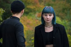 Gothic couple love story. Man and blue hair girl at black clothes at green river background Stock Photo