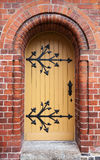Gothic door in red brick wall Stock Image