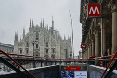 Gothic facade of Milan Cathedral in Piazza del Duomo with lamps and metro sign and M1 line entrance. Milan, Italy - March 1st, 2018: Gothic facade of Milan Royalty Free Stock Photos