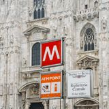 Gothic facade of Milan Cathedral in Piazza del Duomo with lamps and metro sign and M1 line entrance. Milan, Italy - March 1st, 2018: Gothic facade of Milan Royalty Free Stock Image