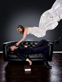 Gothic Fantasy Man Dreaming of Girl. Man dreaming on a couch of a girl in a wedding dress floating and descending to him Royalty Free Stock Photo