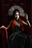 Gothic fashion: young woman sitting in chair and holding glass of wine. Gothic fashion: young woman sitting in chair and holding a glass of wine Royalty Free Stock Photos
