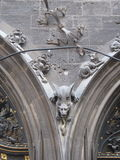 Gothic Gargoyle on arched doorway. Gothic Gargoyle over arched doors in Germany with acanthus leaves and dog Stock Photo