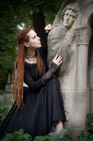 Gothic girl. At cemetery touching the monument Stock Photography