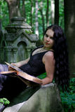 Gothic girl. With old book posing stock images