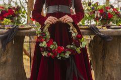 Gothic girl bride wearing a red brocade dress holds a wreath of stock images