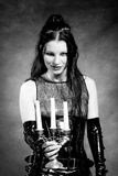 Gothic girl with candles. Gothic girl in latex clothes with candlestick in hands Royalty Free Stock Photo
