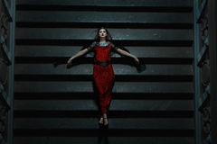 Gothic girl fell on the stairs at night. Stock Photos
