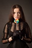 Gothic girl with lollipop. Gothic girl in corset with lollipop over gray Royalty Free Stock Images