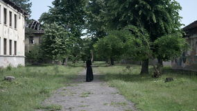 Gothic girl with long hair and a black dress walking between old abandoned buildings stock video