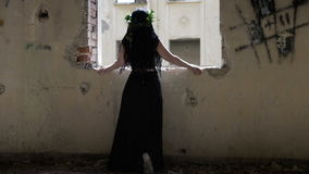 Gothic girl with long hair captive in haunted house standing near a ruined window looking outside. Gothic girl with long hair captive in a haunted house standing stock video