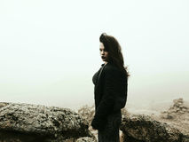 Mysterious woman in foggy mountain. Mysterious woman in black dress and jacket standing in a half - turn on top of  the rock in foggy morning. Gothic atmosphere Stock Image