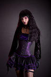 Gothic girl in purple and black outfit. Studio shot on black background Stock Image