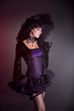 Gothic girl in purple Victorian outfit. Holding umbrella, studio shot on black background royalty free stock photo
