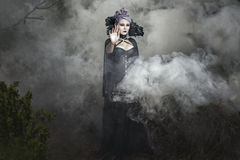 Gothic girl in the smoke. Gothic girl in black clothes stands in the smoke Stock Photography