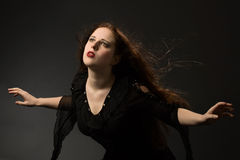 Gothic girl in the wind. Witch flying in the wind on black background Royalty Free Stock Image