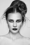 Gothic hairdo. Black and white portrait of young beautiful woman with stylish gothic make-up and hairdo Stock Images