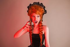 Gothic halloween clothes. Young eerie redhead queen with hairstyle. Death with red hair. Vampire with sharp fangs. Eerie outfit fo. R halloween party. Death stock images