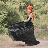 Gothic halloween dress. Young medieval redhead queen with hairstyle. Princess with red hair. Vampire with pale skin. stock photo