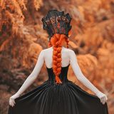 Gothic halloween outfit. Young renaissance queen with hairstyle. Lady with red hair. Renaissance outfit for halloween. Fantastic q. Ueen vampire in gothic gown stock photos