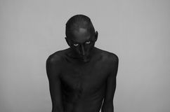 Gothic and Halloween theme: a man with black skin is on a gray background in the studio, the Black Death body art. Gothic and Halloween theme: a man with black royalty free stock images