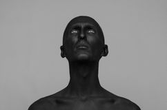 Gothic and Halloween theme: a man with black skin is isolated on a gray background in the studio, the Black Death body art royalty free stock photography