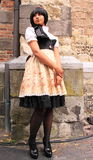 Gothic lolita streetstyle fashion. Beautiful lolita gothic girl showing the clothes she is wearing next to the church wall during the gothic festival summer stock photography