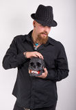 Gothic man with black skull. Man in black holding a black skull stock photos