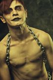 Gothic man. Naked redhead goth with chains over dark background Royalty Free Stock Images